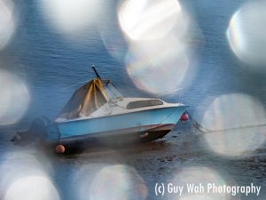 A picture of a boat on the shore at Shoreham beach, taken through broken glass, creating a bokeh effect