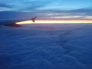 Sunset above the clouds, with an airplane wing in shot too